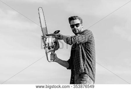 Sharp Blade. Handsome Man With Chainsaw Blue Sky Background. Gardener Lumberjack Equipment. Lumberja