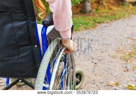 Hand Handicap Woman In Wheelchair Wheel On Road In Hospital Park Waiting For Patient Services. Unrec