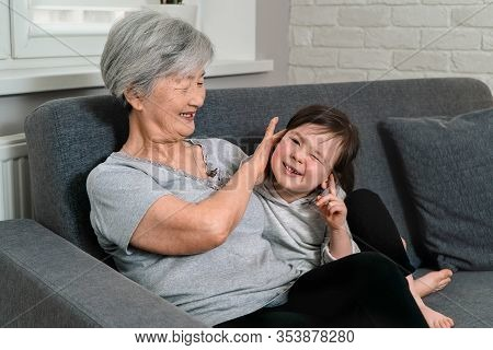 Granddaughter Hugs Her Beloved Grandmother. Great-grandmother With Gray Hair Gently Presses The Grea