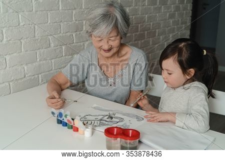 Grandmother And Granddaughter Paint A House In Watercolor. The Grandmother Teaches To Paint The Gran