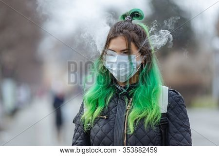 Girl In A Protective Medical Mask And Smokes A Vape.