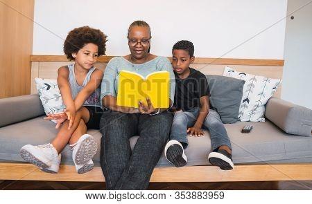 Grandmother Reading A Book To Grandchildren.