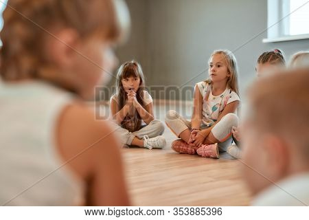 A Group Of Little Cute Girls Sitting On The Floor In The Dance School. Choreography Class. Little Da