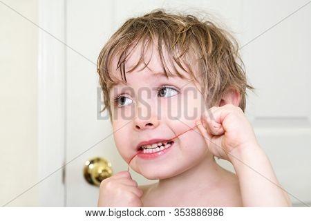 Young boy flossing his teeth, learning dental hygiene