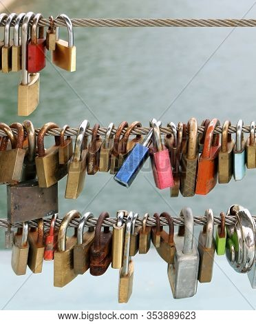 Colorful Rusty Padlocks Left By Sweethearts Locked To A Bridge