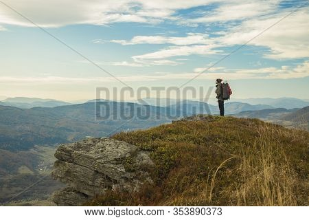 Hiking Mountain Top Edge Of Cliff Highland Scenic View With Backpacker Male Person Stay And Looking