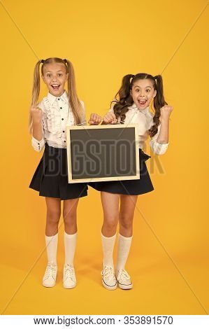 Writing Is Cool. Happy Little Girls Holding Black Writing Surface On Yellow Background. Small Childr
