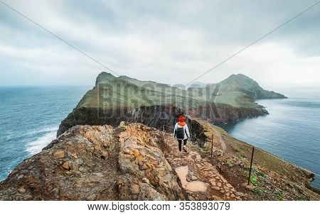 Young Female Backpacker Hiking By Footpath On Sao Lourenco Headland With Atlantic Ocean Bay View In