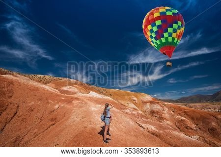 Woman with her son in valley of Mars landscapes in the Altai Mountains, Kyzyl Chin, Siberia, Russia, Aerostat in the sky.