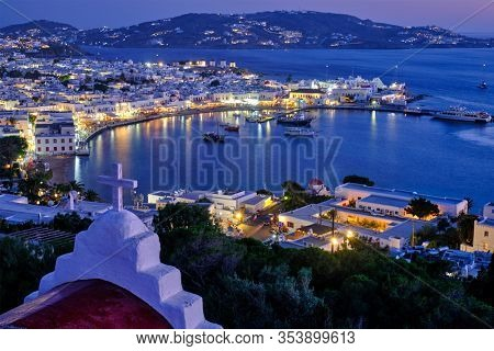 Mykonos town Greek tourist holiday vacation destination with famous windmills port with boats yachts illuminated in evening blue hour with St. Basil church cross. Mykonos, Cyclades islands, Greece