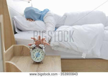 Oversleeping Asian Muslim Woman Wearing White Sleepwear Lying On Bed, Missing Ring Of Alarm Clock Wa