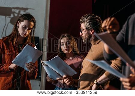 Theater Director, Actor And Actress Rehearsing With Scripts On Stage