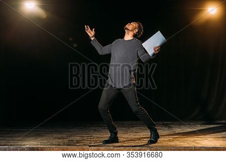 African American Actor Holding Scenario And Standing On Stage During Rehearse In Theatre