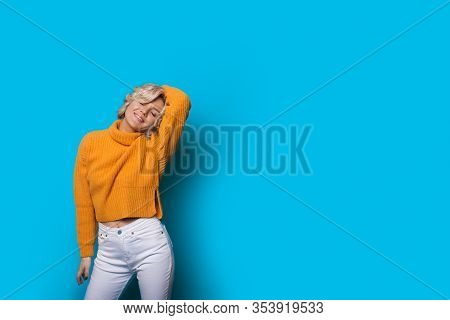 Stretching Blonde Woman Posing In A Yellow Sweater On A Blue Wall With Freespace