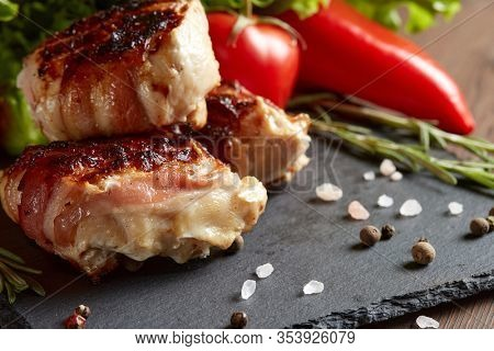 Bacon-wrapped grilled chicken (turkey)  fillet with fresh vegetables and spices on stone cutting board on wooden background