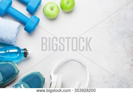 Fitness equipment on a stone background. Top view flat lay with copy space for workout plan