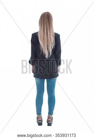 rear view. a young woman in a black blazer, looking at the white wall.