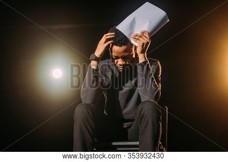 Stressed African American Actor Holding Scenario On Stage During Rehearse