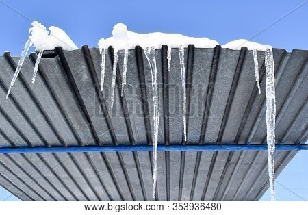 Icicle Sparkles In The Bright Sun. Icicles Hanging From The Roof. Sharp Icicles Hang Down On A Sunny