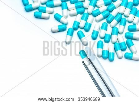 Forceps Pick White-blue Capsule From Group Of Capsule Pills. Drugs Choose. Antibiotic Drug Selection
