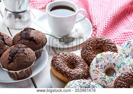 Sweet Breakfast With Chocolate Muffins And Donuts, Cup Of Black Coffee On White Wooden Board Table.