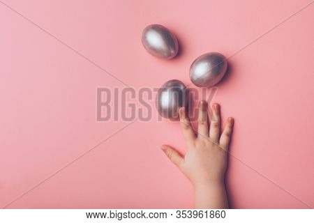 Children's Hand Reaches For Silver Easter Eggs On A Pink Background.