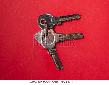 Keys On A Key Chain. Keys Used For Opening Doors Seen From Above, On A Background.