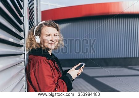 Young Blonde Woman Listening To Music In Wireless Headphones In The Urban Environment, Modern Archit