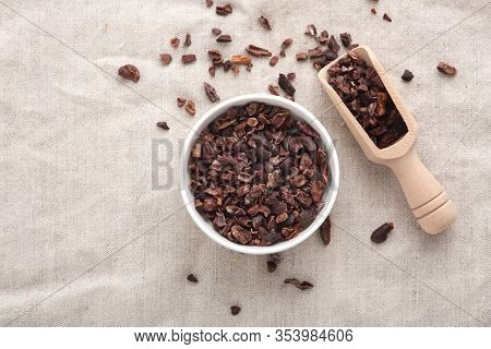 Cacao Nibs In White Bowl With Wooden Scoop