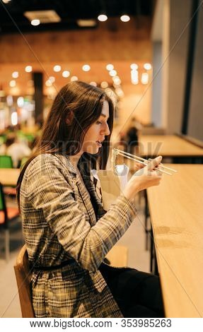 portrait of Real Young pretty woman, eating chinese food with chopsticks