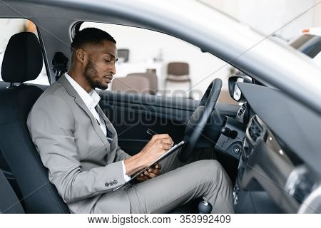 Car Salesman. Black Man Taking Notes Sitting In Drivers Seat In New Automobile Working In Dealership