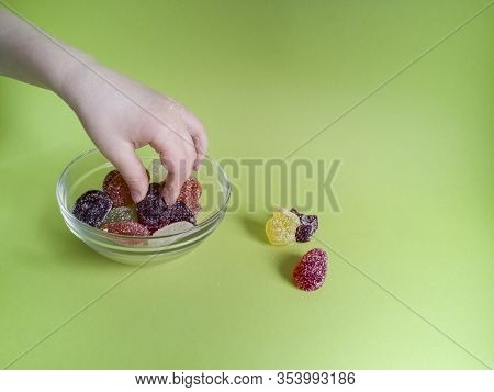 Hand Of Caucasian Child Takes Multicolored Marmalade Candies From Small Glass Bowl On Green Backgrou