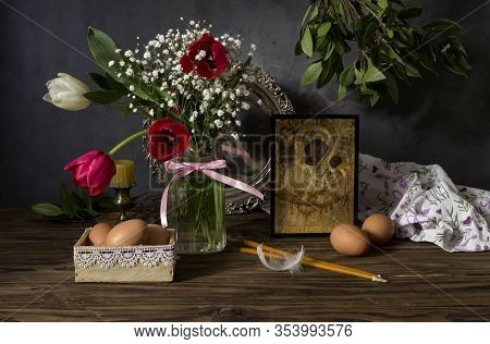 The Easter Composition. Eggs, A Red Tulips, Icon And Church Candles On Wooden Table Close-up.