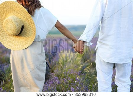 Cute Young Happy Couple In Love In A Field Of Lavender Flowers. Enjoy A Moment Of Happiness And Love