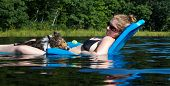 Shetland Sheepdog resting on the lap of a pretty young smiling woman in a bathing suit in a blue floating chair on a lake. poster