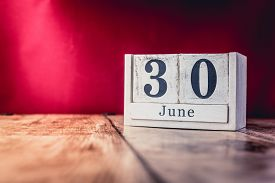 June 30th. Day 30 Of Month, Calendar On Business Office Table, Workplace With Vivid Maroon Red Backg