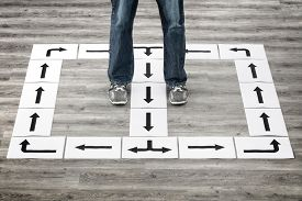 Taking strategy decisions for the future man standing with many direction arrow choices, left, right or move forward or go around in circles