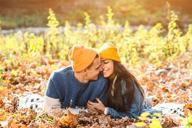 Lovely Couple Lies On The Ground In Autumn Leaves. Stylish Fashion Couple Kissing Outdoors In Autumn