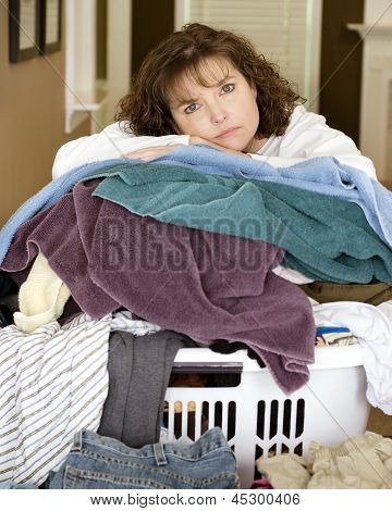 Unhappy, sad, tired woman resting on large, messy pile of laundry