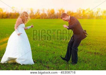 bride and groom sunlight dancing merrily in green field, couple,