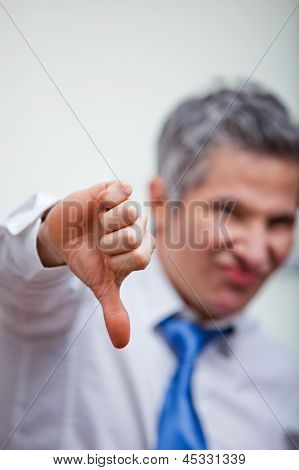 Businessman gesturing thumbs down sign