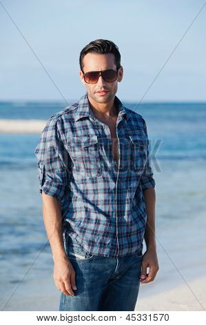 Man wearing sunglasses and standing on the beach