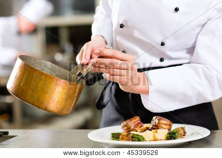 Female Chef in hotel or restaurant kitchen cooking, only hands to be seen, she is working on the sauce for the food as saucier