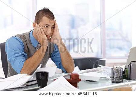 Troubled businessman sitting at desk covered with documents, chin in hand, thinking of problems.
