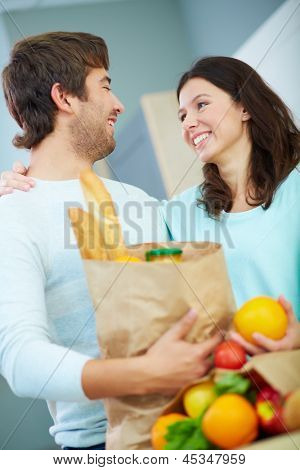 Young couple with paperbags looking at one another with smiles