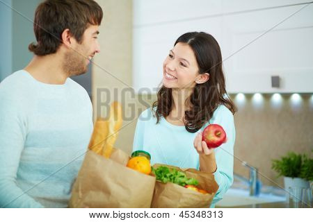 Pretty female and her husband with paper packets interacting in the kitchen