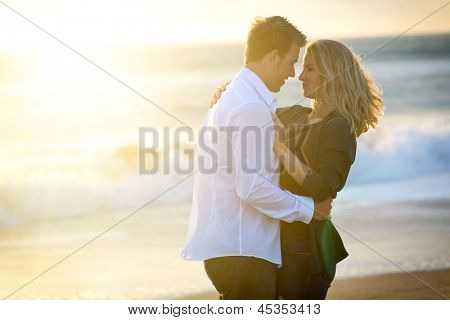 Young loving couple at the beach at sunset