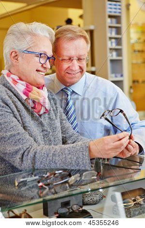 Two happy seniors buying new glasses at optician retail store