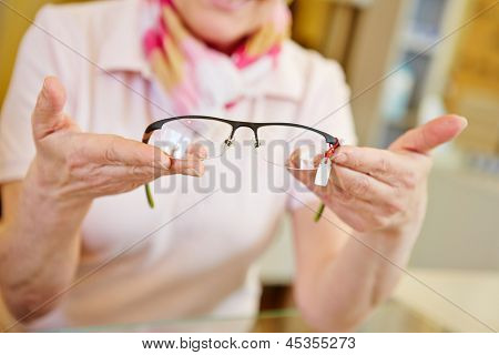 Hands of optician offering new fashionable glasses