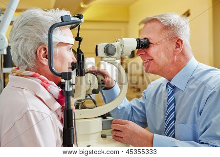 Ophthalmologist examing cornea of senior woman with slit lamp